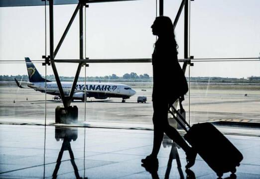 Mujer andando por el aeropuerto con un avión de Ryanair en la pista de aterrizaje
